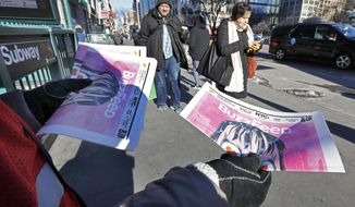 Brand ambassador Camila Marte distributes copies of a BuzzFeed newspaper at a subway station near New York's Union Square, Wednesday, March 6, 2019. The internet and social media company printed a one-time, special edition BuzzFeed newspaper, showcasing the latest news stories and BuzzFeed content. (AP Photo/Richard Drew)