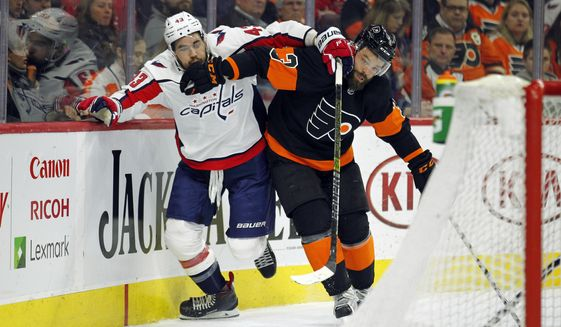 Washington Capitals' Tom Wilson, left, and Philadelphia Flyers' Radko Gudas chase the puck behind the Flyers' net during the first period of an NHL hockey game Wednesday, March 6, 2019, in Philadelphia. (AP Photo/Tom Mihalek)