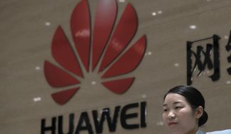 A woman stands at the reception counter of the Huawei's Cyber Security Lab Huawei factory in Dongguan, China's Guangdong province, Wednesday, March 6, 2019. Huawei Technologies Co. is one of the world's biggest supplier of telecommunications equipment. (AP Photo/Kin Cheung)