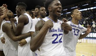 RETRANSMISSION TO CHANGE TO SECOND HALF - Seton Hall guard Myles Cale (22) and guard Shavar Reynolds (33) celebrate with teammates after defeating Marquette during the second half of an NCAA college basketball game, Wednesday, March 6, 2019, in Newark, N.J. Seton Hall won 73-64. (AP Photo/Julio Cortez)