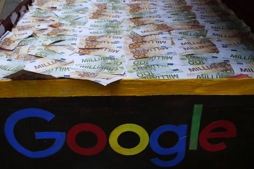 FILE - In this Jan.31, 2019 file photo, a trunk full of fake bank notes is displayed as activists from anti-globalization organisation Attac stage a protest at Google's Paris headquarters to criticize the company's tax evasion policies, in Paris. The French government is unveiling plans to slap a 3 percent tax on the French revenues of internet giants like Google, Amazon and Facebook. (AP Photo/Francois Mori, File)