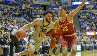 West Virginia guard Jermaine Haley (10) works the ball past Iowa State guard Tyrese Haliburton (22) during the first half of an NCAA college basketball game Wednesday, March 6, 2019, in Morgantown, W.Va. (William Wotring/The Dominion-Post via AP)