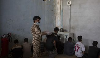 FILE - In this Oct. 3, 2017 file photo, a Kurdish security officer orders a displaced man from Hawija to sit down as they try to determine if the men being held were associated with the Islamic State group, at a Kurdish screening center in Dibis, Iraq. In a report released Wednesday, March 6, 2019, Human Rights Watch said Iraqi and Kurdistan Regional Government authorities have charged hundreds of children with terrorism for alleged affiliation with IS, often using torture to coerce confessions. (AP Photo/Bram Janssen, File)