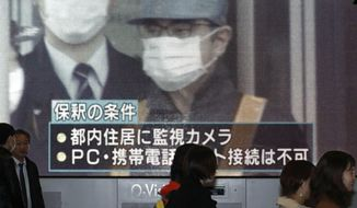 """People walk by a monitor which reports on the bail of former chairman of Nissan Motor Co., Carlos Ghosn, in Osaka, western Japan Wednesday, March 6, 2019. Disguised as a construction worker, Ghosn left a Tokyo detention center Wednesday after posting 1 billion yen ($8.9 million) bail. The letters, bottom, read """" Conditions for his release."""" (Kyodo News via AP)"""