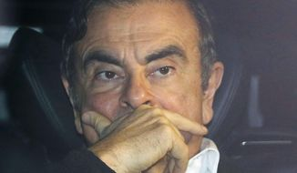 Former Nissan chairman Carlos Ghosn rides in a car from a building Wednesday, March 6, 2019, in Tokyo, after posting 1 billion yen ($8.9 million) in bail once an appeal by prosecutors against his release was rejected. Ghosn, the star auto executive credited with rescuing both Renault and Nissan, left a drab Tokyo detention center Wednesday after more than three months in custody, his identity obscured by a surgical mask, hat and construction worker's outfit.(Takuya Inaba/Kyodo News via AP) **FILE**