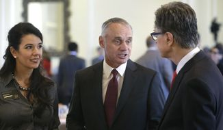 Major League Baseball Commissioner Rob Manfred, center, speaks with Boston Red Sox owner John Henry, right, and Boston Globe Managing Director Linda Henry, left, at a gathering of the Boston College Chief Executives Club, Wednesday, March 6, 2019, in Boston. (AP Photo/Steven Senne)