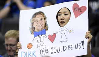 A Dirk Nowitzki fan holds up a sign before an NBA basketball game between the Washington Wizards and the Dallas Mavericks, Wednesday, March 6, 2019, in Washington. (AP Photo/Nick Wass)