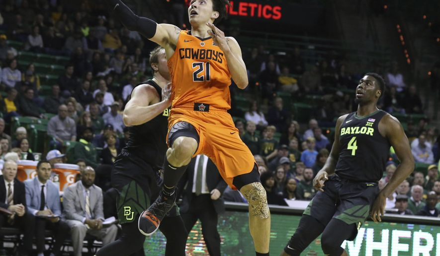 Oklahoma State guard Lindy Waters III, center, scores between Baylor guard Makai Mason, left, and guard Mario Kegler, right, in the first half of an NCAA college basketball game, Wednesday, March 6, 2019, in Waco, Texas. (Rod Aydelotte/Waco Tribune Herald, via AP)