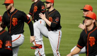 FILE - In this Feb. 15, 2019, file photo, San Francisco Giants catcher Joey Bart, center, works out during a spring training baseball practice, in Scottsdale, Ariz. The Giants' Joey Bart already looks like a big leaguer in his first camp. The same with Nick Madrigal of the White Sox and the four college pitchers the Royals chose within the first 40 selections last season. Perhaps they are the beginning of a trend toward quick-to-the-bigs draft picks _ guys who can provide rather immediate help not unlike the NFL or the NBA. (AP Photo/Matt York, File)