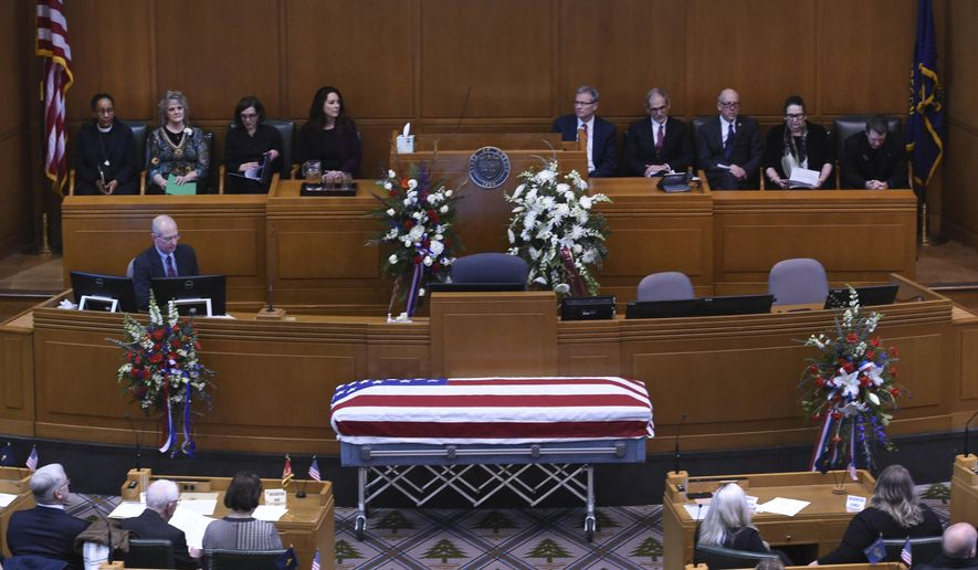 The casket of Oregon Secretary of State Dennis Richardson is surrounded by family, legislators and the public in the House Chambers during the state funeral at the Oregon State Capitol in Salem, Ore., Wednesday, March 6, 2019. (AP Photo/Steve Dykes)