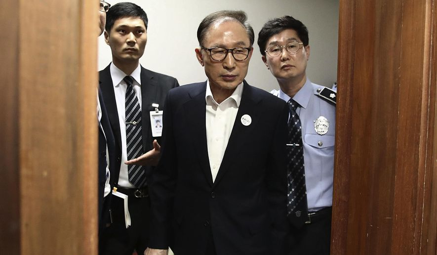 FILE - In this May 23, 2018, file photo, former South Korean President Lee Myung-bak, center, appears for his first trial at the Seoul Central District Court in Seoul, South Korea. A South Korean court on Wednesday, March 6, 2019, has approved the release of Lee on 1 billion won ($885,000) bail during his ongoing corruption trial. (Chung Sung-Jun/Pool Photo via AP, File)