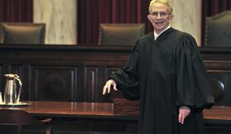 FILE - In this Jan. 5, 2012 file photo, West Virginia Supreme Court of Appeals Chief Justice Menis Ketchum poses in his robe in the court chambers in Charleston, W.Va. The former West Virginia Supreme Court justice is due in court for sentencing for using a state vehicle and gas fuel card for a 2014 golf trip to Virginia. Ex-Justice Ketchum's sentencing is scheduled Wednesday, March 6, 2019, in federal court in Charleston. (Bob Wojcieszak /The Daily Mail via AP, File)
