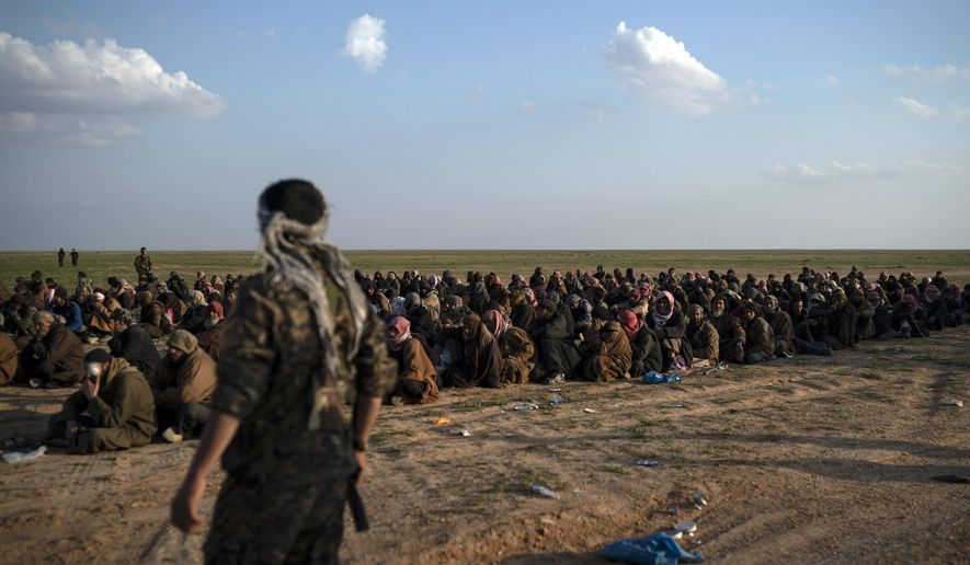 In this Friday, Feb. 22, 2019, file photo, U.S.-backed Syrian Democratic Forces (SDF) fighters stand guard next to men waiting to be screened after being evacuated out of the last territory held by Islamic State group militants, near Baghouz, eastern Syria. Even as they face imminent defeat, militants of the IS have remained organized and ruthless to their last breath, keeping their institutions functioning as best they can. (AP Photo/Felipe Dana, File)