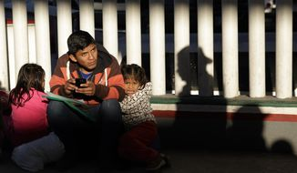 FILE - In this Jan. 25, 2019, file photo, a migrant who did not give his name looks on with his children as they wait to hear if their number is called to apply for asylum in the United States, at the border in Tijuana, Mexico. The Trump administration's effort to make asylum seekers wait in Mexico explicitly targets Spanish-speakers and people from Latin America, according to internal guidelines of a highly touted strategy to address the burgeoning number of Central Americans arriving at U.S. borders. (AP Photo/Gregory Bull, File)