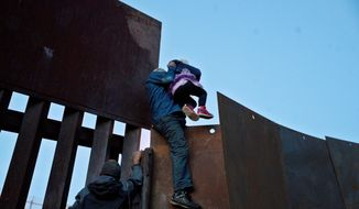 FILE - In this Dec. 2, 2018 file photo, a Honduran migrant helps a young girl cross to the American side of the border wall, in Tijuana, Mexico. A San Diego TV station says the U.S. government ran an operation to screen journalists, activists and others while investigating last year's migrant caravan from Mexico. KNSD-TV says documents leaked by a Homeland Security source show a January database listing at least 10 journalists, seven of them U.S. citizens, as warranting secondary screening at U.S. points of entry. (AP Photo/Ramon Espinosa, File)