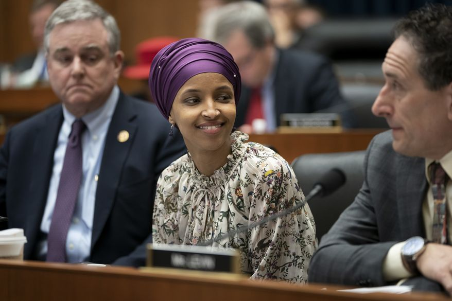 """Rep. Ilhan Omar, D-Minn., sits with fellow Democrats, Rep. David Trone, D-Md., left, and Rep. Andy Levin, D-Mich., right, on the House Education and Labor Committee during a bill markup, on Capitol Hill in Washington, Wednesday, March 6, 2019. Omar stirred controversy last week saying that Israel's supporters are pushing U.S. lawmakers to take a pledge of """"allegiance to a foreign country."""" Omar is not apologizing for that remark, and progressives are supporting her. (AP Photo/J. Scott Applewhite) **FILE**"""