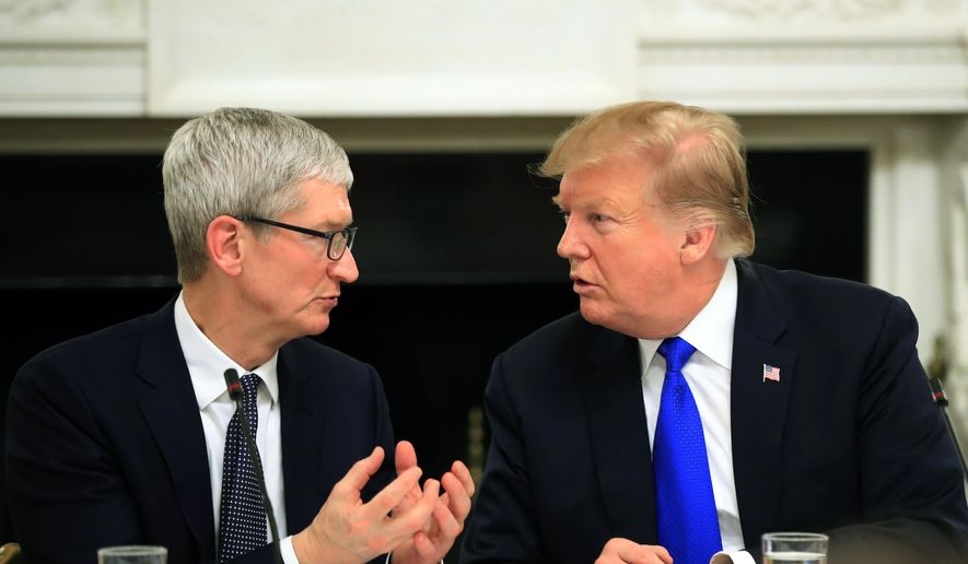 In this Wednesday, March 6, 2019 file photo, President Donald Trump talks to Apple Inc. CEO Tim Cook during the American Workforce Policy Advisory Board's first meeting in the State Dining Room of the White House in Washington. (AP Photo/Manuel Balce Ceneta, File)