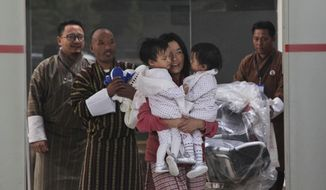 Bhumchu Zangmo walks out of the airport carrying her children, conjoined Bhutanese twin sisters Nima and Dawa, followed by their father Sonam Tshering in Paro, Bhutan, Thursday, March 7, 2019. Twenty-months-olds Nima and Dawa flew from Melbourne with their mother Thursday, months after a surgical separation. The girls had been joined at the torso and shared a liver. They were separated in a procedure at Melbourne's Royal Children's Hospital early November. (AP Photo/Karan Gurung)