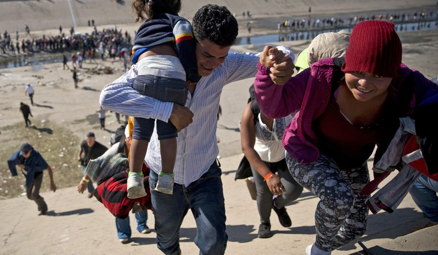 In this Nov. 25, 2018, photo, migrants walk up a riverbank at the Mexico-U.S. border after getting past a line of Mexican police at the Chaparral border crossing in Tijuana, Mexico, as they try to reach the U.S. A San Diego TV station says the U.S. government ran an operation to screen journalists, activists and others while investigating last year's migrant caravan from Mexico. KNSD-TV says documents leaked by a Homeland Security source show a January database listing at least 10 journalists, seven of them U.S. citizens, as warranting secondary screening at U.S. points of entry. (AP Photo/Ramon Espinosa) **FILE**