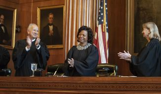 Associate Justices Paul Newby and Robin Hudson applaud for new Chief Justice Cheri Beasley, center, of the N.C. Supreme Court during Beasley's investiture ceremony in Raleigh on Thursday, March 7, 2019. (Paul Woolverton/The Fayetteville Observer via AP)