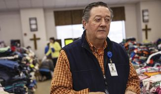 In this Wednesday, March 6, 2019, photo, Rusty Sowell, pastor at Providence Baptist Church, speaks to volunteers organizing donations at the church in Beauregard, Ala. Dealing with the dead became a huge task in a rural Alabama community where nearly two dozen people died in a tornado outbreak. The county coroner, Bill Harris, set up a temporary command post and performed post-mortem exams. He and Sowell then held 17 separate meetings with relatives of the 23 people who died. (AP Photo/David Goldman)