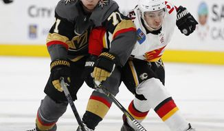 Vegas Golden Knights center William Karlsson (71) and Calgary Flames left wing Johnny Gaudreau (13) vie for the puck during the third period of an NHL hockey game Wednesday, March 6, 2019, in Las Vegas. (AP Photo/John Locher)