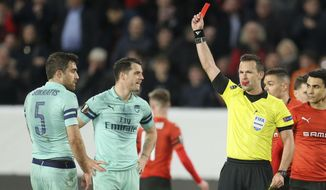 Ivan Kruzliak of Slovakia shows the red card to Arsenal's Sokratis Papastathopoulos, left, during the Europa League round of 16, first leg soccer match between Rennes and Arsenal at Roazhon Park in Rennes, northwestern France, Thursday, March 7, 2019. (AP Photo/David Vincent)