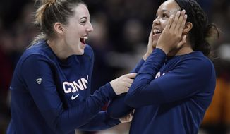 Connecticut seniors Katie Lou Samuelson, left, and Napheesa Collier share a light moment as their numbers are revealed on the Huskies of Honor wall during an NCAA college basketball game against Houston, Saturday, March 2, 2019, in Storrs, Conn. (AP Photo/Jessica Hill)
