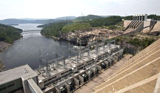 """FILE - In this June 22, 2010 file photo, the Jean-Lesage hydro electric dam generates power along the Manicouagan River north of Baie-Comeau, Quebec. A proposed transmission line across western Maine to serve as a conduit for Canadian hydropower is """"in the best interest"""" of state electricity customers thanks to incentives negotiated with Central Maine Power, the state's public advocate said on Thursday, March 7, 2019. (Jacques Boissinot/The Canadian Press via AP, File)"""