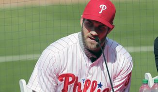 FILE - In this Saturday, March 2, 2019 file photo, Bryce Harper speaks during a news conference at the Philadelphia Phillies spring training baseball facility in Clearwater, Fla. For years, the NL East has been soft as a bunt single. Not anymore.. Even before Bryce Harper decided to stay in the division, four of the five teams spent this offseason swinging for the fences. In addition to defending champion Atlanta, the New York Mets, Philadelphia Phillies and Washington Nationals all have enough firepower to potentially contend for the playoffs. (AP Photo/Lynne Sladky, File)