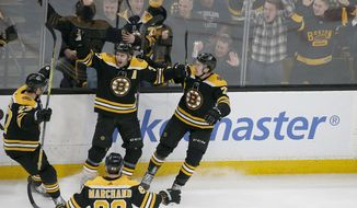 Boston Bruins center Patrice Bergeron (37) is congratulated by teammates after scoring a goal during the third period of an NHL hockey game against the Florida Panthers, Thursday, March 7, 2019, in Boston. (AP Photo/Mary Schwalm)