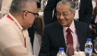 Malaysian Prime Minister Mahathir Mohamad, right, talks with Philippine Secretary of Trade and Industry Ramon Lopez during a business forum at the financial district of Makati, metropolitan Manila, Philippines on Thursday, March 7, 2019. (AP Photo/Aaron Favila)