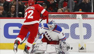 Detroit Red Wings center Andreas Athanasiou scores a shootout goal against New York Rangers goaltender Henrik Lundqvist (30) during an NHL hockey game Thursday, March 7, 2019, in Detroit. Detroit won 3-2. (AP Photo/Paul Sancya)