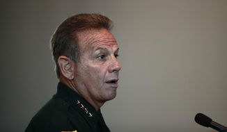 In this Thursday, Nov. 15, 2018, file photo, Broward County Sheriff Scott Israel speaks before the state commission in Sunrise, Fla.  Israel, who was suspended by the governor and accused of failing to prevent the Parkland school shooting filed suit Thursday, March 7, 2019, seeking his job back and alleging Gov. Ron DeSantis improperly ousted him for political reasons. (AP Photo/Brynn Anderson, File)