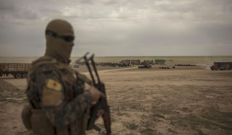 In this Wednesday, March 6, 2019, photo, a member of U.S.-backed Syrian Democratic Forces (SDF) stands guard at a reception area for people evacuated from the last shred of territory held by Islamic State militants, outside Baghouz, Syria. (AP Photo/Gabriel Chaim)