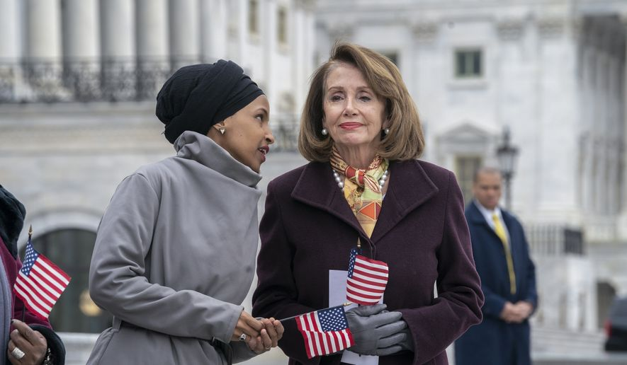 "Rep. Ilhan Omar, D-Minn., left, whispers to Speaker of the House Nancy Pelosi, D-Calif., as Democrats rally outside the Capitol ahead of passage of H.R. 1, ""The For the People Act,"" a bill which aims to expand voting rights and strengthen ethics rules, in Washington, Friday, March 8, 2019. The House passed a resolution to condemn anti-Semitism and other bigotry on Thursday following debate over Omar's recent comments suggesting House supporters of Israel have dual allegiances. (AP Photo/J. Scott Applewhite)"