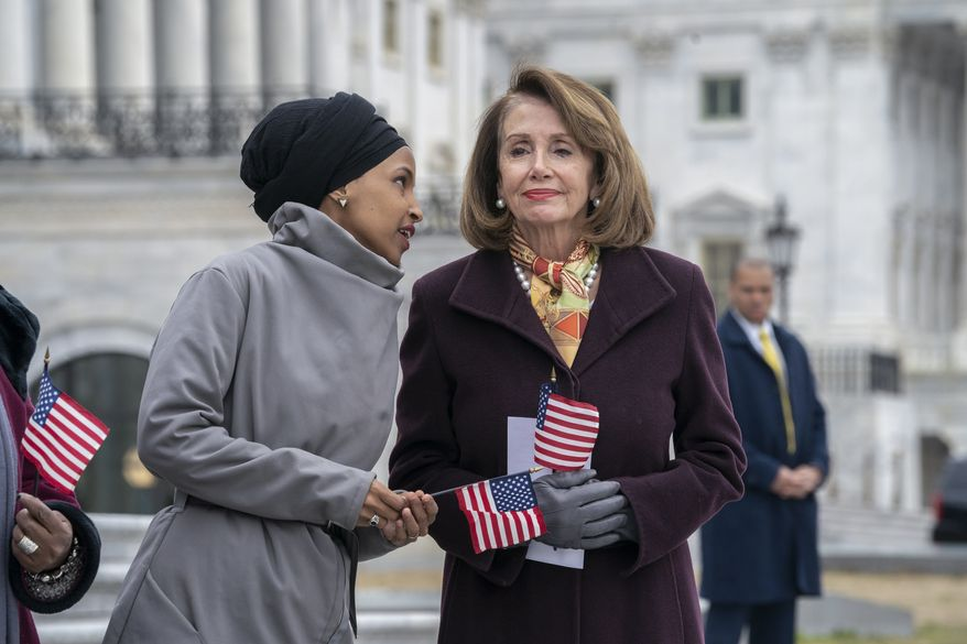 """Rep. Ilhan Omar, D-Minn., left, whispers to Speaker of the House Nancy Pelosi, D-Calif., as Democrats rally outside the Capitol ahead of passage of H.R. 1, """"The For the People Act,"""" a bill which aims to expand voting rights and strengthen ethics rules, in Washington, Friday, March 8, 2019. (AP Photo/J. Scott Applewhite) **FILE**"""