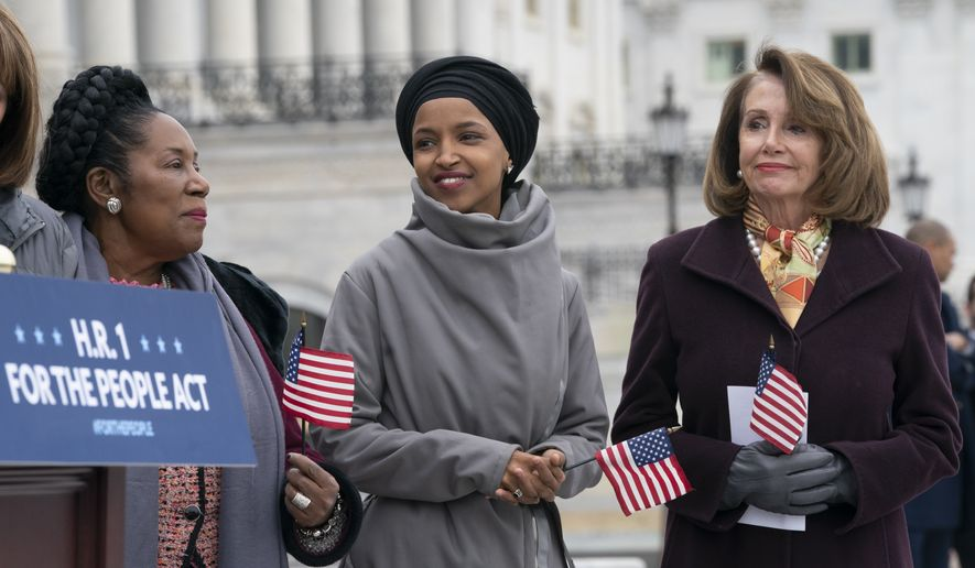 "Rep. Ilhan Omar, D-Minn., smiles as she stands between Rep. Sheila Jackson Lee, D-Texas, left, and Speaker of the House Nancy Pelosi, D-Calif., as Democrats rally outside the Capitol ahead of passage of H.R. 1, ""The For the People Act,"" a bill which aims to expand voting rights and strengthen ethics rules, in Washington, Friday, March 8, 2019. (AP Photo/J. Scott Applewhite)"