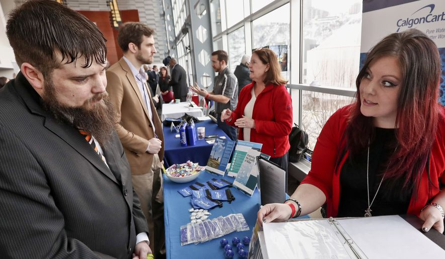 In this Thursday, March 7, 2019, photo visitors to the Pittsburgh veterans job fair meet with recruiters at Heinz Field in Pittsburgh. (AP Photo/Keith Srakocic)