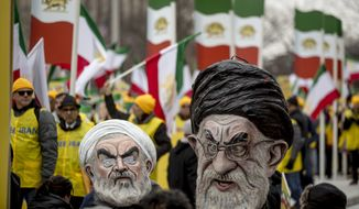 Two people dressed as Iranian President Hassan Rouhani, left, and Iran's supreme Leader Ayatollah Ali Khamenei, right, walk through Freedom Plaza during an Organization of Iranian-American Communities rally in Washington, Friday, March 8, 2019. (AP Photo/Andrew Harnik)