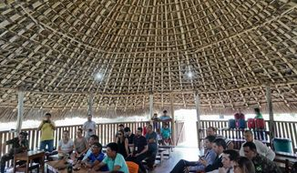 "Temehe Tomas Waimiri, sitting center left and wearing blue shirt and glasses, gives testimony about alleged crimes committed by the Brazilian dictatorship in the 1970s, during a hearing inside a traditional ""maloca"" indigenous hut, at the Waimiri-Atroari reserve in Amazon state, Wednesday, Feb. 27, 2019. Temehe Tomas said he saw a group of soldiers attacking by land and helicopters dropping bombs. ""The attackers had uniforms of the color of the jungle,"" he said. (AP Photo/Victor R. Caivano)"
