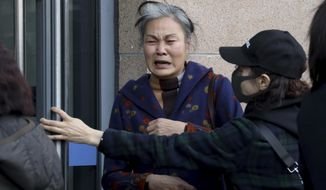 A relative of passengers on board the missing Malaysia Airlines Flight 370 (MH370) weeps after a meeting with Chinese Foreign Ministry officials in Beijing, Friday, March 8, 2019. Friday marked the fifth anniversary of the disappearance of MH370, which vanished March 8, 2014 while en route from Kuala Lumpur to Beijing. (AP Photo/Ng Han Guan)