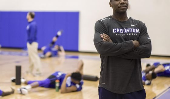 FILE - In this March 17, 2017, file photo, Creighton assistant coach Preston Murphy, right, stands as players warm up during practice in Omaha, Neb. Creighton has placed Murphy on administrative leave after he was implicated in a sting in which he allegedly took a $6,000 from an aspiring sports agent to send clients his way. Athletic director Bruce Rasmussen said in a statement Friday night, March 8, 2019, that Murphy would be on leave pending an internal review. (AP Photo/Nati Harnik, File)