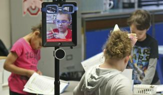 In this Thursday, Feb. 28, 2019 photo, Levi Suttles, 6, displayed on a monitor, is still able to attend school at Miami View School in South Charleston, Ohio, despite battling leukemia thanks to a robot designed by the Ohio State University engineering department. The robot allows Levi to move around and interact with his class from a computer at home. (Bill Lackey/The Springfield News-Sun via AP)