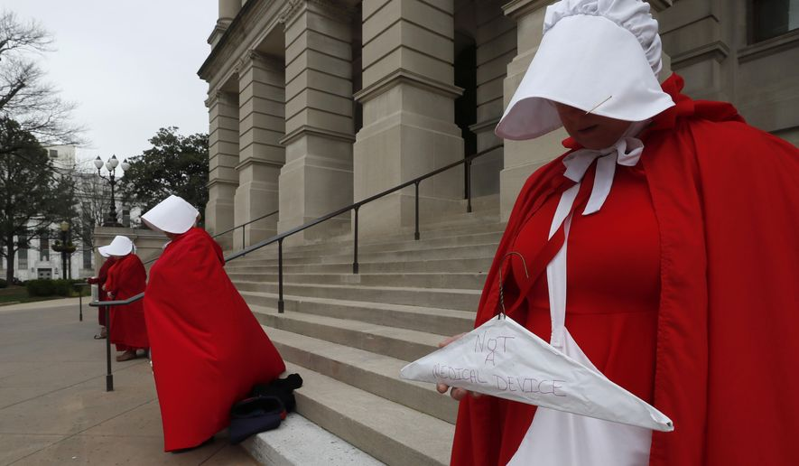 Georgia members of the Handmaid Coalition protest the passage of HB 481 outside the Capitol, Friday, March 8, 2019, in Atlanta. Now that the House has passed HB 481, the Senate is now tasked with tackling legislation that would ban most abortions after 6 weeks. The House approved the legislation late Thursday and advocates on both sides of the issues have already begun pushing senators to vote their way. (Bob Andres/Atlanta Journal-Constitution via AP)