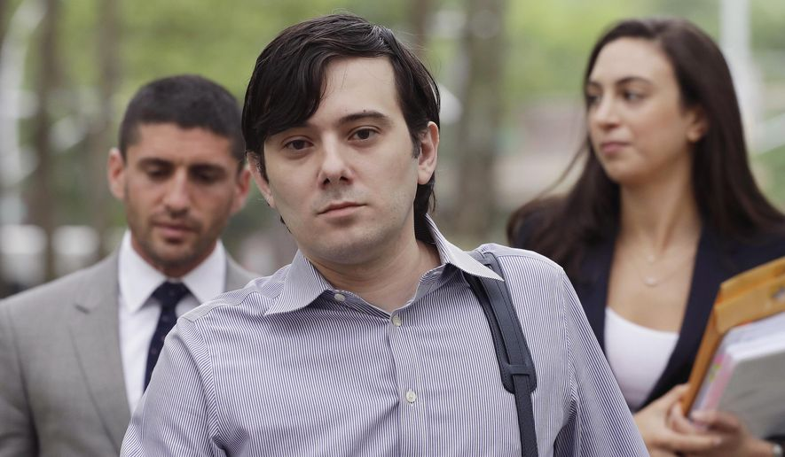 """FILE - In this June 19, 2017, file photo, former Turing Pharmaceuticals CEO Martin Shkreli, center, arrives at Brooklyn federal court in New York with members of his legal team. Federal authorities are investigating claims that Shkreli has been running his pharmaceutical company from behind bars. The U.S. Bureau of Prisons said Friday, March 8, 2019, that it has opened an inquiry into whether the so-called """"Pharma Bro"""" used a contraband smartphone inside a federal prison in New jersey. (AP Photo/Mark Lennihan, File)"""