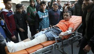 Medics and relatives move a wounded teenager, who was shot by Israeli troops during a protest at the Gaza Strip's border with Israel, into the treatment room of Shifa hospital in Gaza City, Friday, March 8, 2019. (AP Photo/Adel Hana)