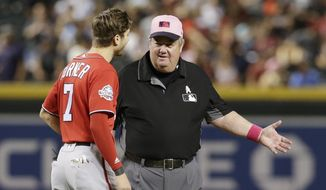 FILE - In this May 13, 2018, file photo, MLB umpire Joe West, right, talks with a player in the ninth inning during a baseball game between the Arizona Diamondbacks and the Washington Nationals in Phoenix. West, who has umpired more than 5,000 big league games, said the 2016 TrackMan computer system test was far from perfect. (AP Photo/Rick Scuteri, File)