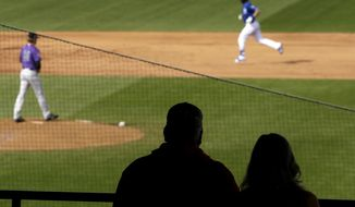 Fans in the stands and Colorado Rockies pitcher Sam Howard, left, watch as Kansas City Royals' Bubba Starling rounds the bases after hitting a solo home run during the fifth inning of a spring training baseball game Monday, Feb. 25, 2019, in Surprise, Ariz. (AP Photo/Charlie Riedel)