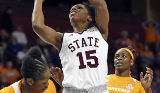 Mississippi State's Teaira McCowan (15) shoots over Tennessee's Zaay Green, left, and Cheridene Green during the first half of an NCAA college basketball game at the Southeastern Conference women's tournament, Friday, March 8, 2019, in Greenville, S.C. (AP Photo/Richard Shiro)